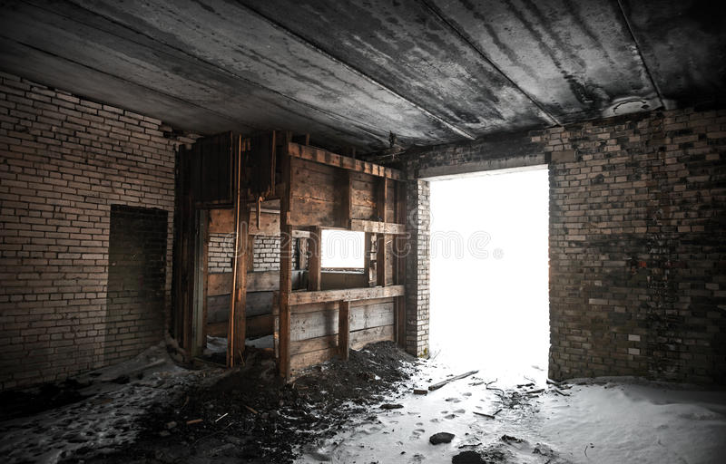 Old grunge abandoned barn interior. With glowing exit stock photography