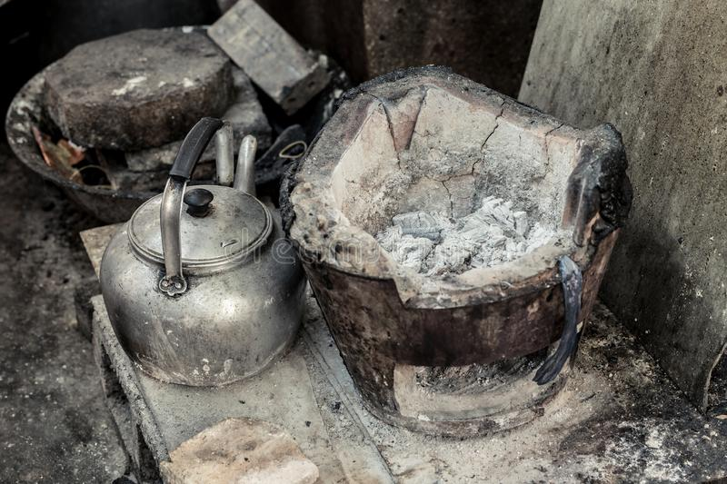 Old grunge asian stove with burn charcoal and kettle pot royalty free stock photos