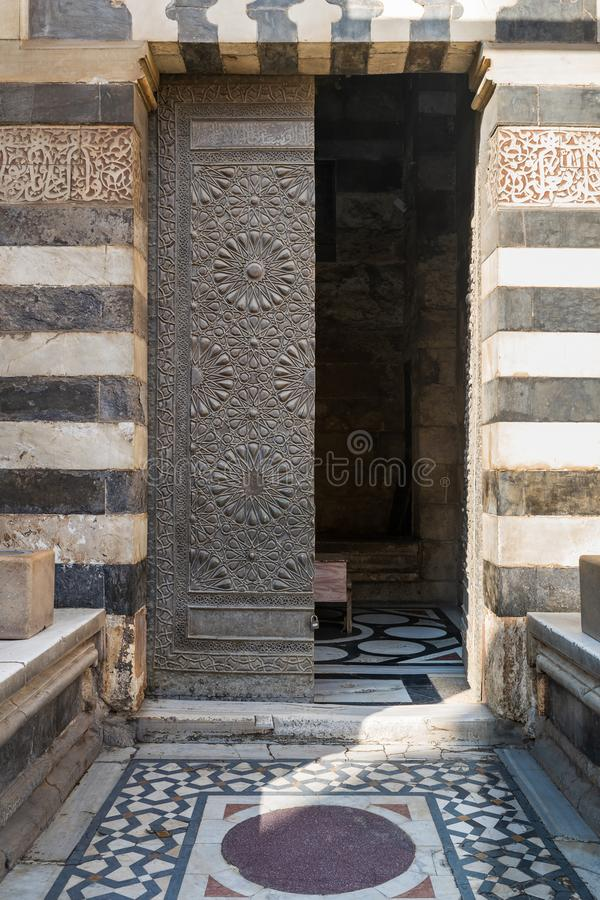 Old grunge decorated bronze-plate door surrounded by striped black and white marble decorations. And stone wall at public historic mosque of Sultan Barquq, El stock photo