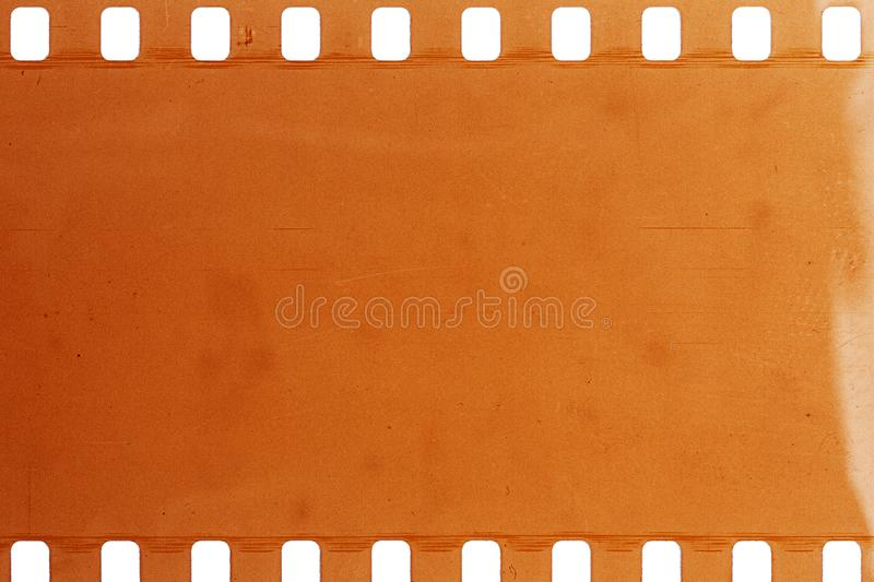 Old grunge filmstrip. Blank yellow vibrant noisy filmstrip isolated on white background royalty free stock images