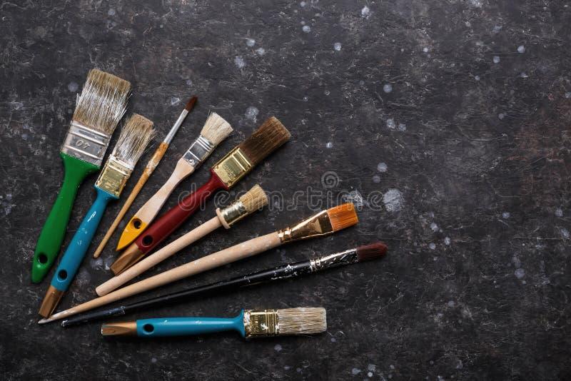 Old paint brushes set on dark gray grunge background. stock photos