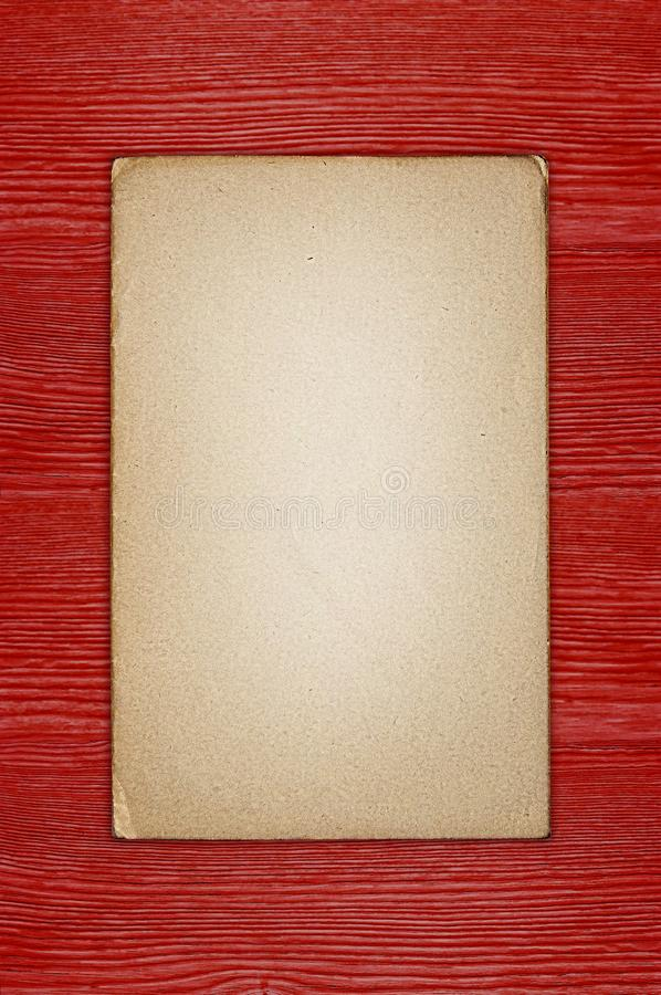 Old grunge paper on the red wood texture stock image