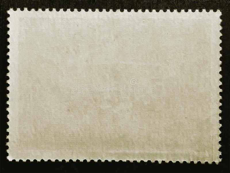 Old grunge texture paper posted stamp reverse side isolated on black background. Close up. Copy space royalty free stock photography