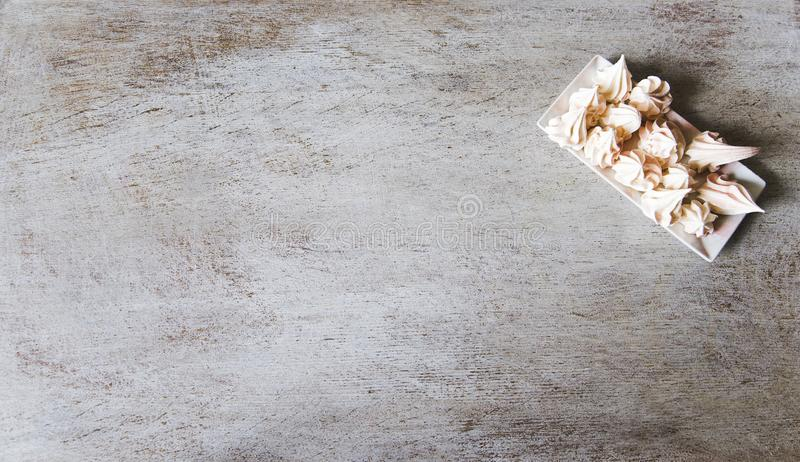 Old grunge textures backgrounds. Meringues on a white square plate. Perfect background with space royalty free stock photography