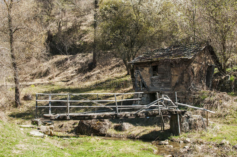 Old grunge village house and bridge. Rural mountain landscape with old grunge dilapidated ramshackle house and small wooden bridge in early springtime royalty free stock images