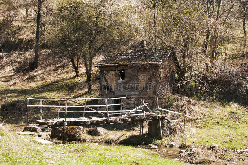 Old grunge village house and bridge. Rural mountain landscape with old grunge dilapidated ramshackle house and small wooden bridge in early springtime stock images