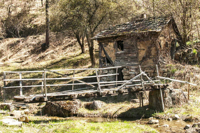 Old grunge village house and bridge. Rural mountain landscape with old grunge dilapidated ramshackle house and small wooden bridge in early springtime royalty free stock photography