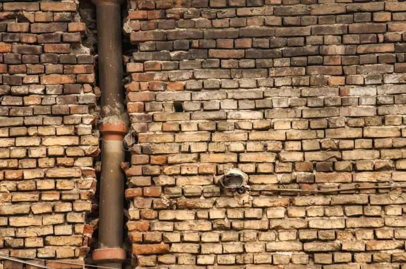 Old grunge weathered brickwall with ceramic sewer. Old grunge weathered brickwall with stoneware vitrified clay ceramic drain sewer pipe closeup stock images