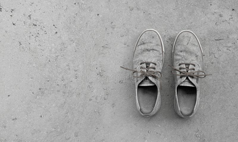 Old grungy camouflage shoes on concrete background stock photo