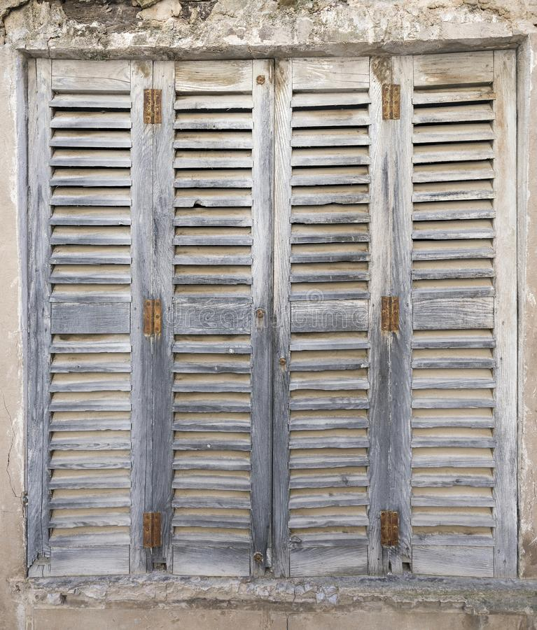 Old grungy grey shutters with rusty hinges in broken wall stock photography