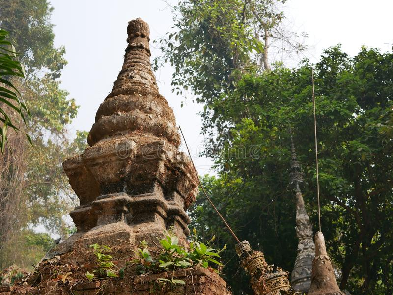 Old grungy small pagoda  chedi  abandoned in a forest - Buddhist religious architecture. Old grungy small pagoda  chedi  abandoned in a forest. - Buddhist royalty free stock photos