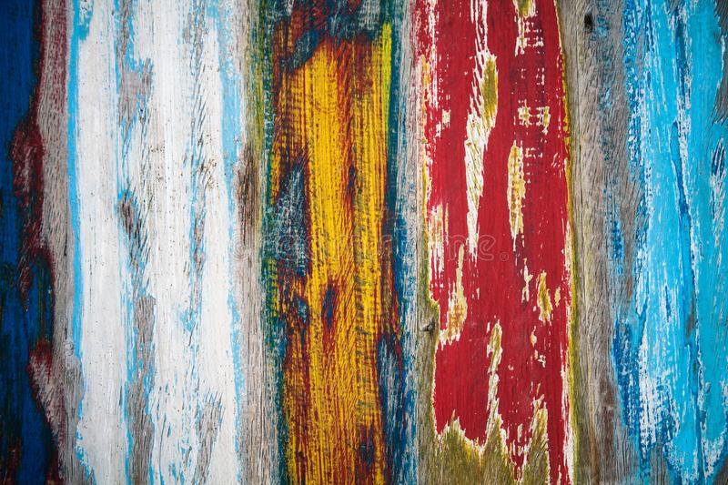 Old grungy weathered colourfully painted wooden wall plank texture in yellow, blue, red and white color mix artistic background royalty free stock photography