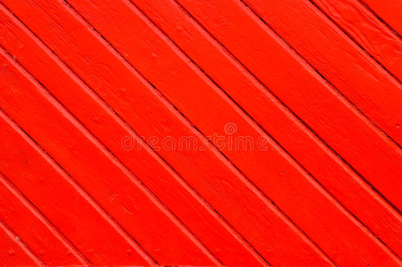 Old grungy and weathered red orange painted wood wall plank in diagonal to the frame as simple saturated background texture. Old grungy and weathered red orange royalty free stock images