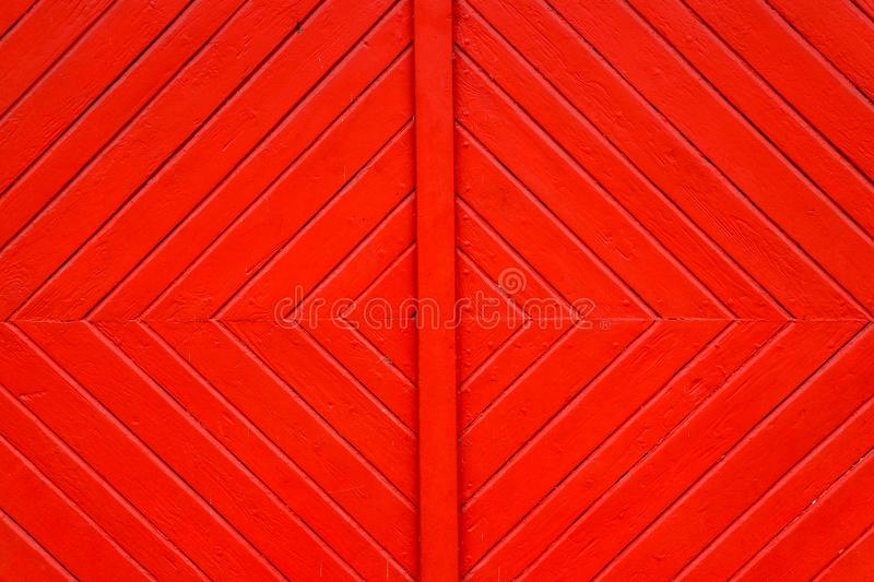Old grungy and weathered red orange painted wooden wall plank door detail with diagonal lines forming squares as simple saturated. Intense colored wood surface stock photography