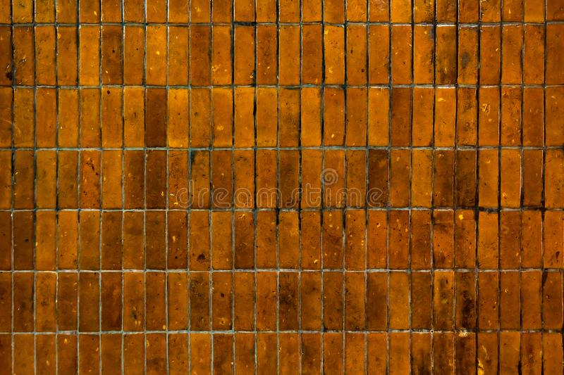 Old grungy yellow ceramic tile bricks wall in urban. royalty free stock photography