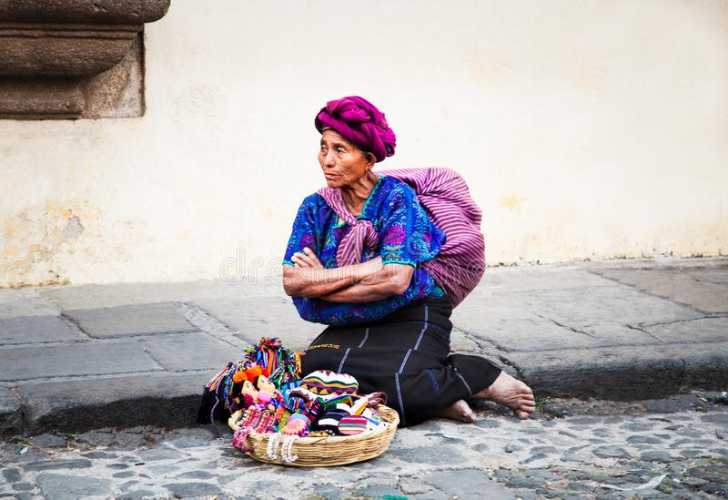 Old guatamalian woman salling traditional goods at the street in. ANTIGUA, GUATEMALA-DEC 26, 2015: : Old guatamalian woman salling traditional goods at the royalty free stock image