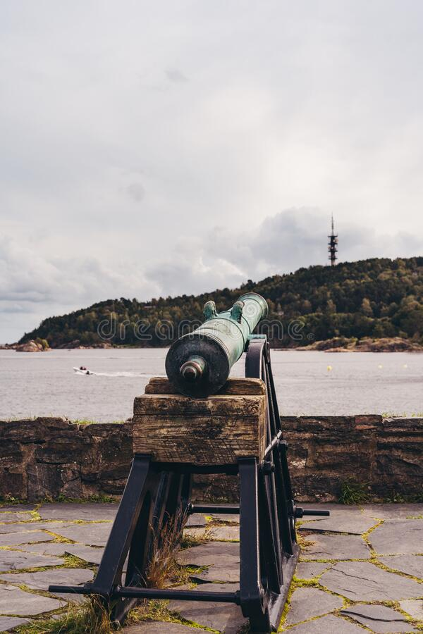 Gun pointing out to the sea at the Christiansholm Fortress in Kristiansand Norway. Old gun pointing out to the sea at the Christiansholm Fortress that is stock photo