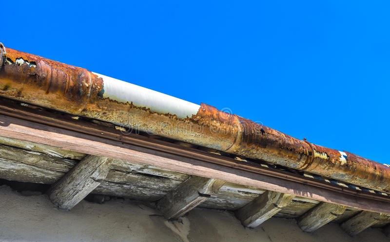 Old gutter. A broken gutter on the roof of a house stock photos