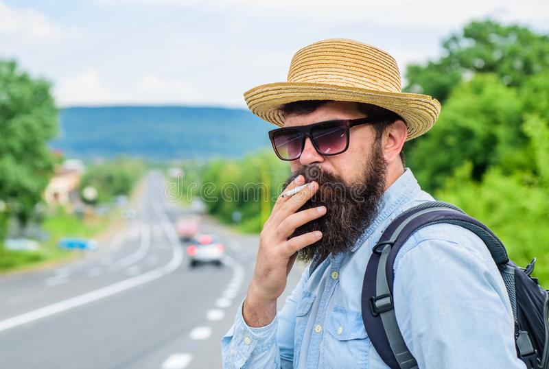 Old habit. Man with beard and mustache in straw hat smoking cigarette, road background defocused. Traveler stylish stock photos