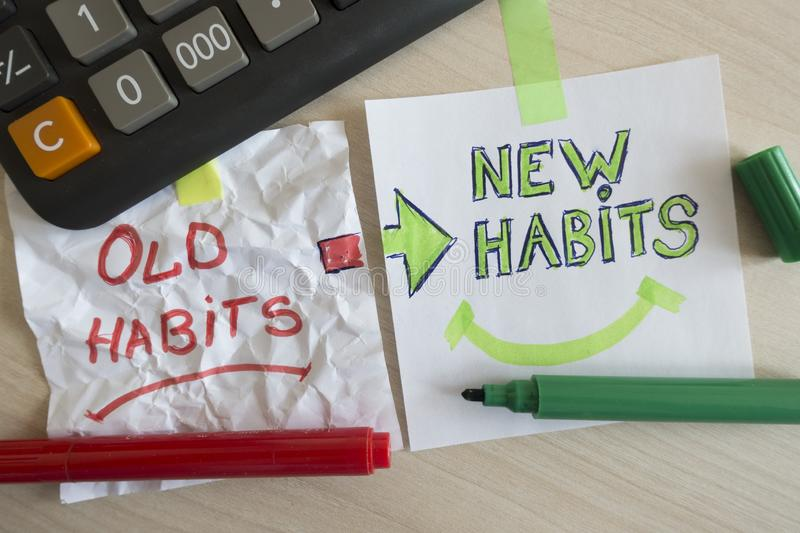 Old habits and new habits handwritten on white pieces of paper at the office royalty free stock photo