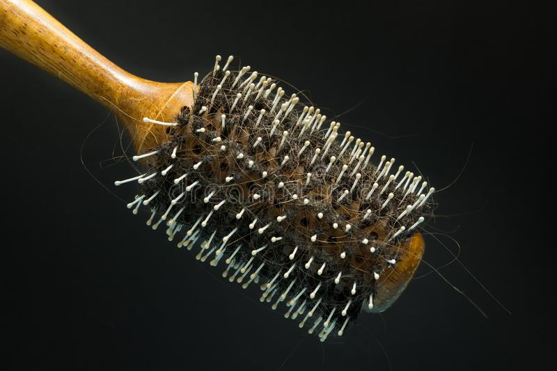An old hairbrush with fallen hair on a black background, hygiene and hair loss royalty free stock photo