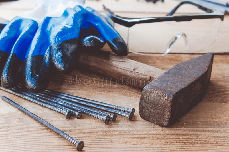 Old hammer with nails with blue gloves and glasses to protect the eyes on a blackboard background. Tools for construction work royalty free stock photo