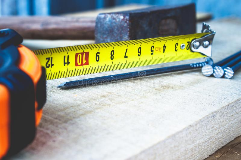 Old hammer with nails and a yellow ruler of roulette on a blackboard background. Tools for construction work. Close-up stock image