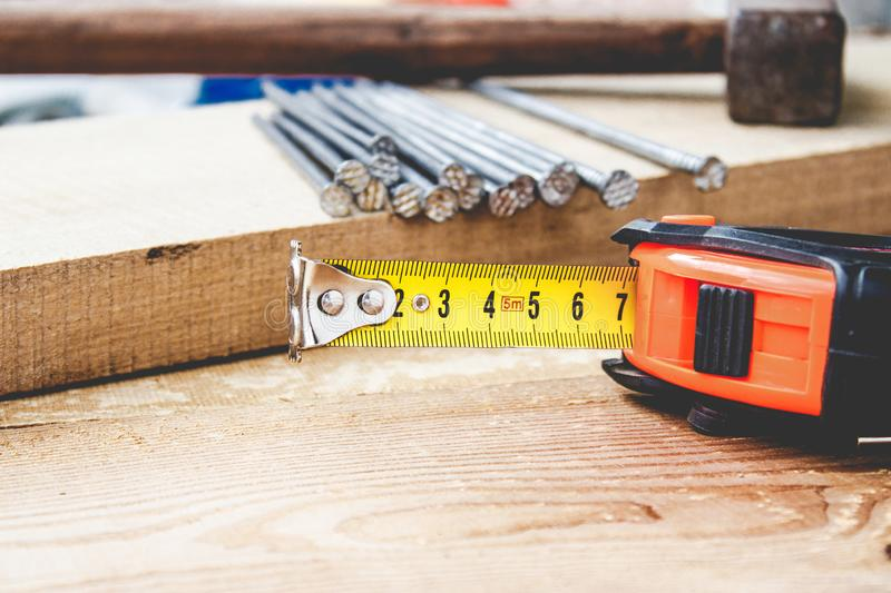 Old hammer with nails and a yellow ruler of roulette on a blackboard background. Tools for construction work. Close-up stock photo