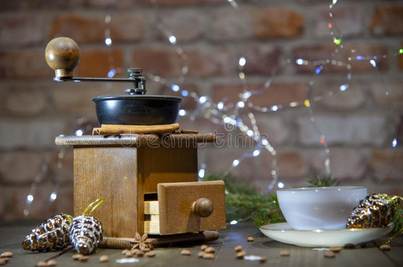 An old manual coffee grinder and a porcelain Cup against a brick wall. New year in loft style. An old hand-held coffee grinder and a porcelain Cup against a royalty free stock photo