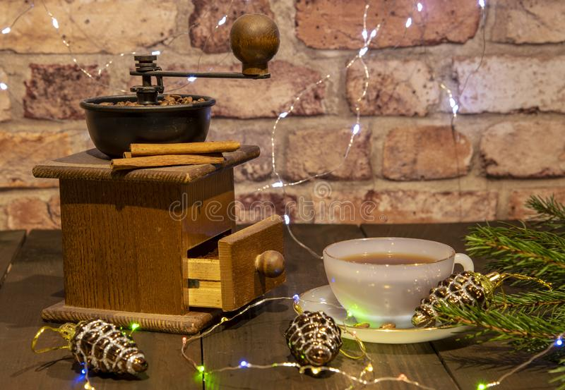 An old hand-held coffee grinder and a porcelain Cup against a brick wall. Decorated with Christmas toys, lanterns and fir branches. New year in loft style royalty free stock images