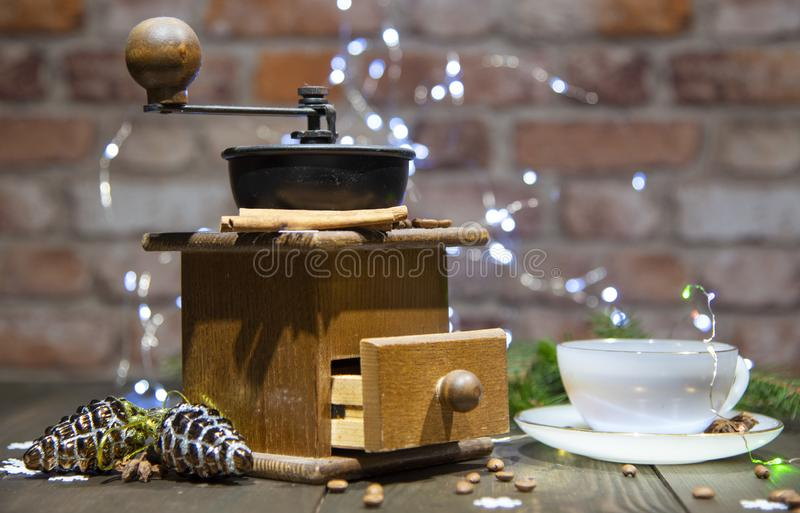 An old hand-held coffee grinder and a porcelain Cup against a brick wall. Decorated with Christmas toys, lanterns and fir branches. New year in loft style stock photos