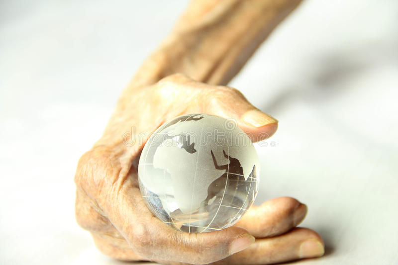 Old hand held a crystal clear globe. Old aged human hand held a crystal clear globe stock photos