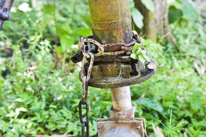Old hand pump water supply lock by cane safety royalty free stock photos