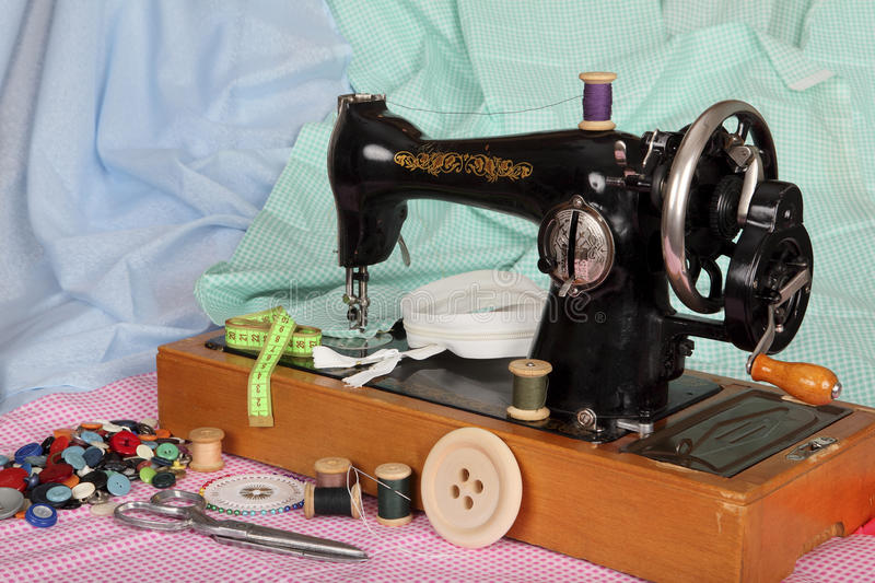 An old, hand sewing machine with a needle, retro coils with colored threads, bright buttons and pieces of colored cotton fabric royalty free stock photography