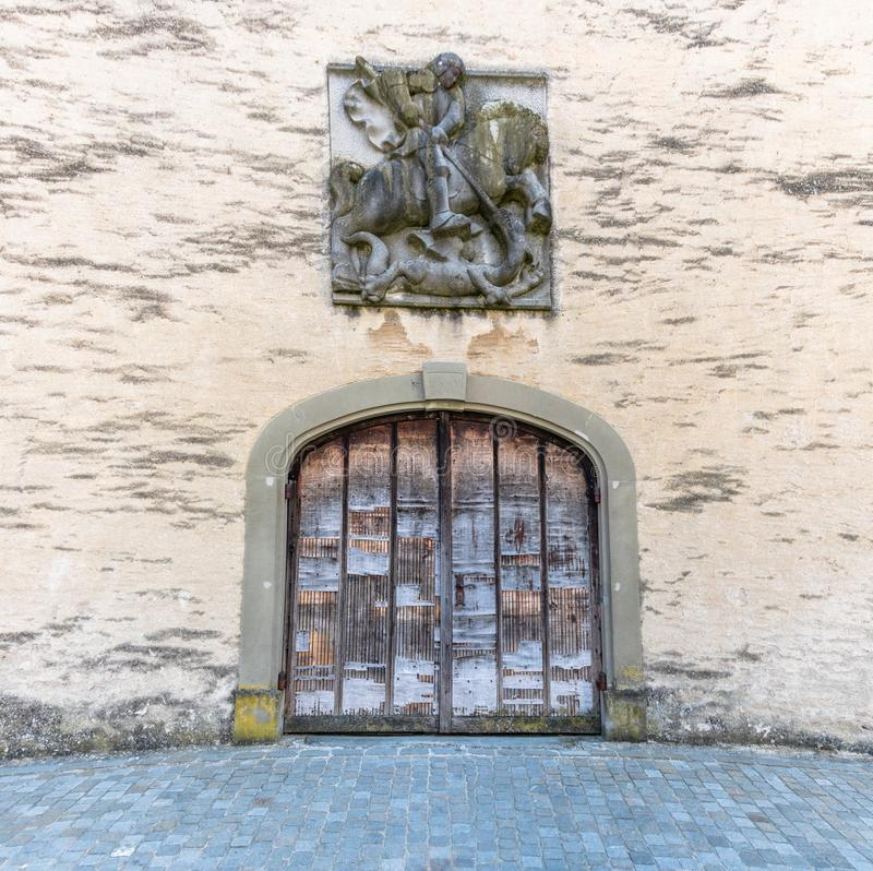Old handmade medieval wooden gate with a commemorative town seal above in an idyllic small European village royalty free stock image