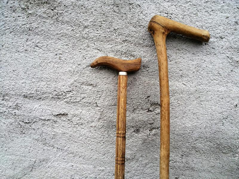 Handmade wooden walking sticks standing on the wall. Old handmade wooden walking sticks standing on the gray rough wall royalty free stock image
