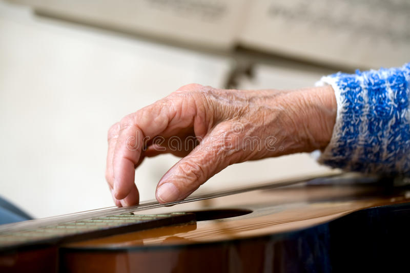 Old hands on guitar stock image