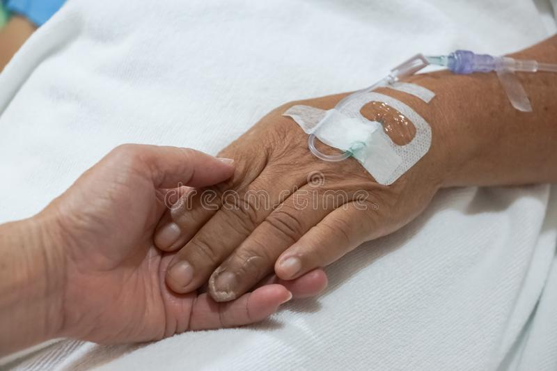 Old hands holding each other with IV solution stock photography
