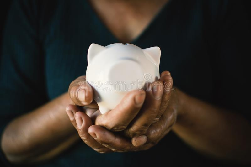 Old hands holding white piggy bank on darkness stock photos