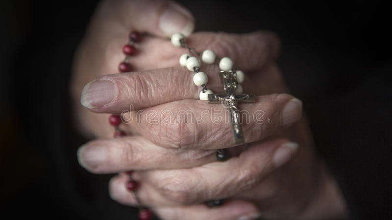 Old hands praying and holding a rosary stock image