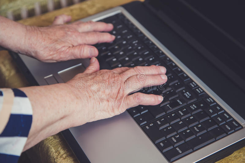 Old hands typing on laptop stock image