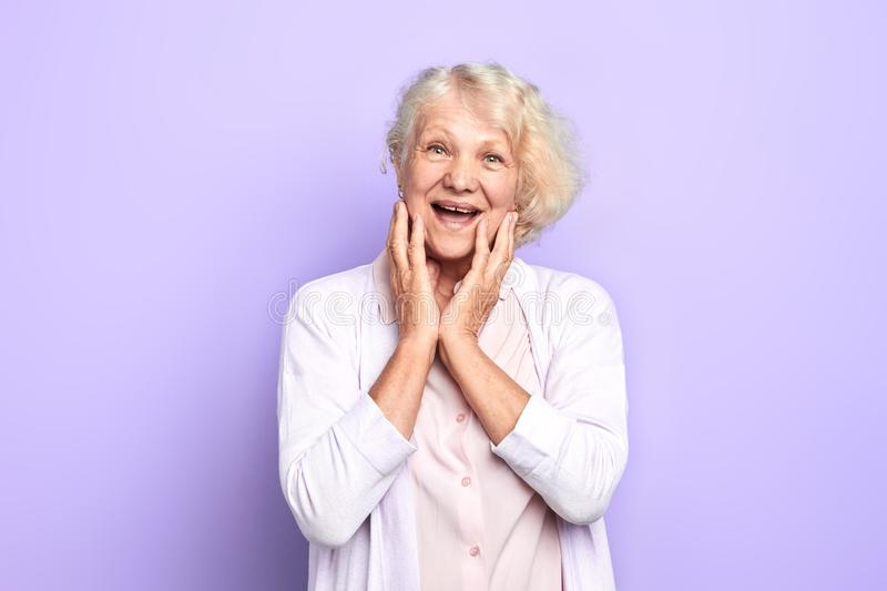 Old happy blonde woman touching her face with palms stock images