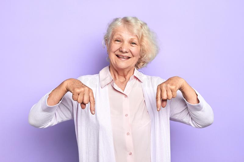 An old happy lady female doctor pointing down on a copy space. royalty free stock photos
