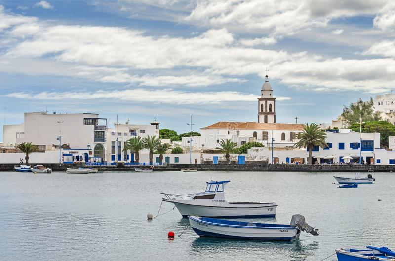 Old harbor of Arrecife with boats and the sixteenth century catholic church San Gines de Clermont. Arrecife, Spain - November 5, 2018: Waterfront of the town royalty free stock image