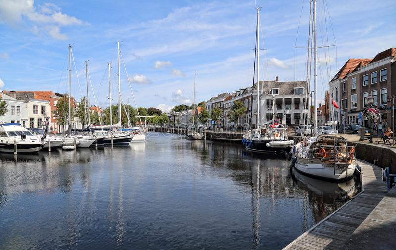 Old harbor of Goes in the Netherlands. Goes, The Netherlands - August 24, 2017: Recreational sailboats lie moored and people sit on benches in the old harbor of royalty free stock photography