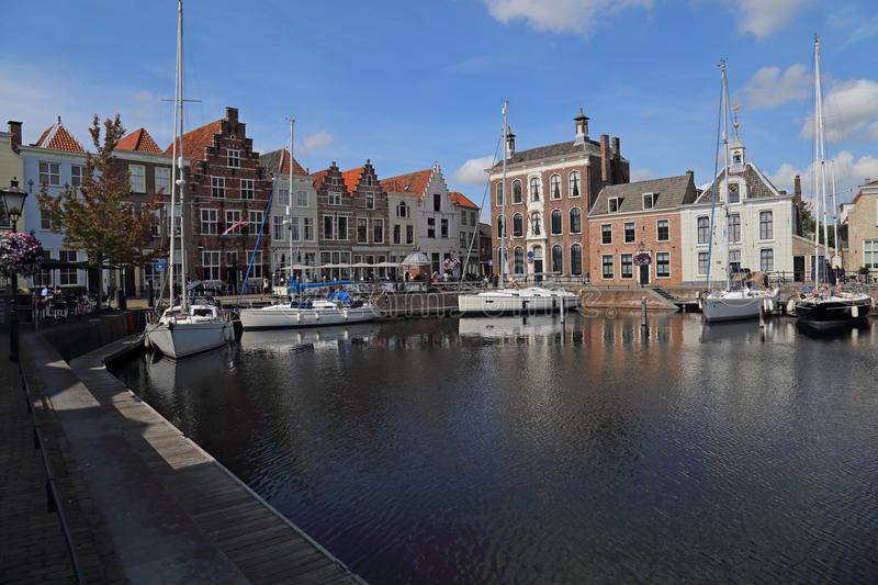 Old harbor of Goes in the Netherlands. Goes, The Netherlands - August 24, 2017: Recreational sailboats moored to the quay and people sit at restaurants in the stock photography
