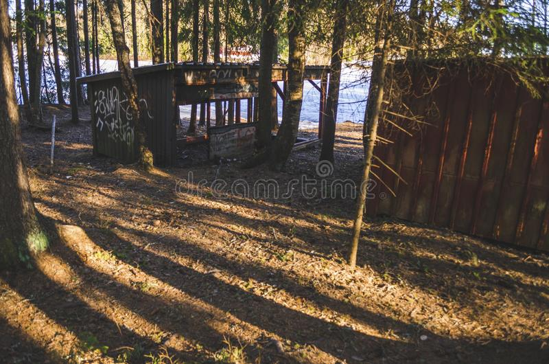 Old haunted desserted damaged hut in a jungle landscape painted with white ink in nature during the winter. In a beautiful sunny day royalty free stock photo