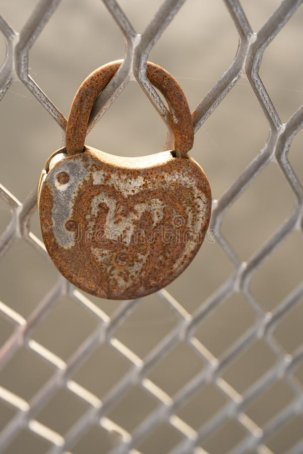 Old heart shaped rusty padlock on metal fence stock photo