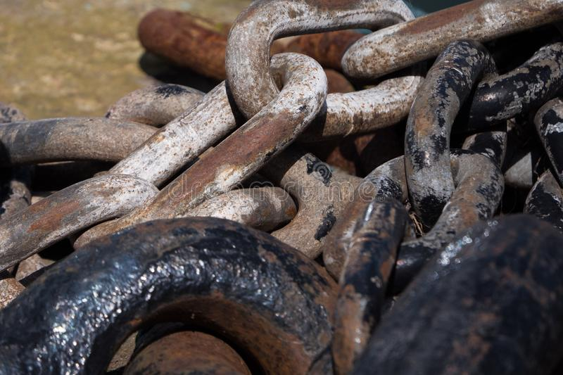 Old, heavy, rusty, iron chains in an unused dock stock photo
