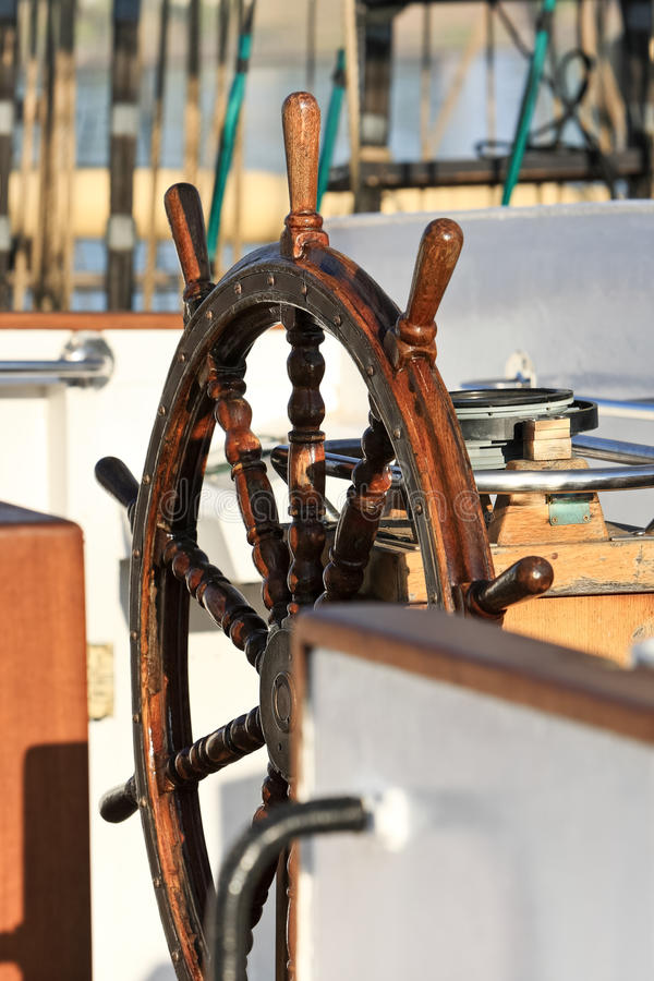 Old helm on sailing ship in sunrise light royalty free stock images